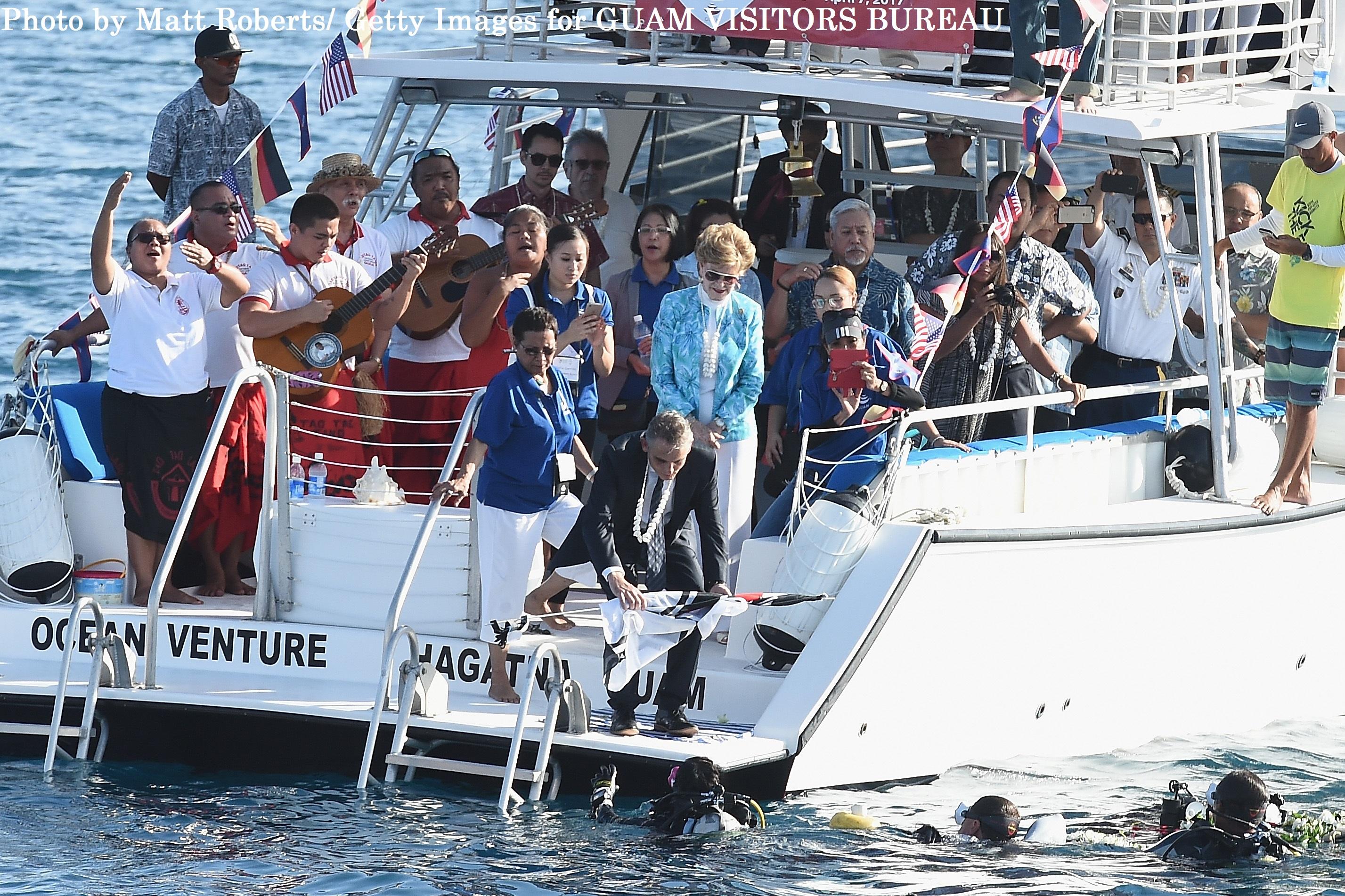 アプラ湾で4 ⽉7 ⽇朝、開催された「SMS コーモラン Ⅱ」沈没100 周年記念式典にて、 ドイツの旗をダイバーに⼿渡す駐マニラドイツ⼤使館、⼤使館員マイケル・ハスパー⽒