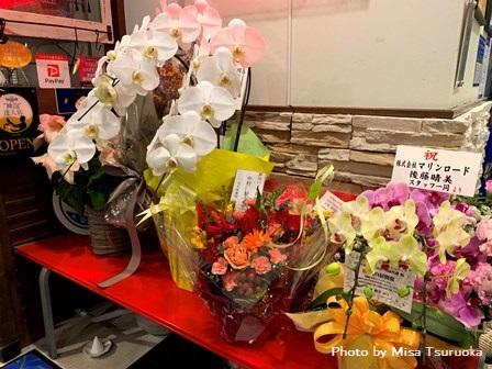 お店の入口にはたくさんのお祝いのお花が! 本当に開催おめでとうございます