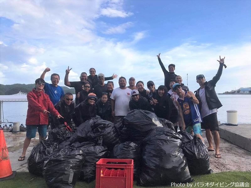 2回目の水中清掃に集まったガイドダイバーたちと、当日回収されたごみを詰めた30ガロンのごみ袋の数々